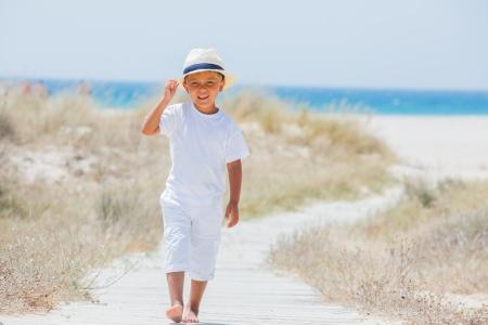 Cute happy boy in hat walking the beach  On background sea  photo