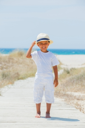 Cute happy boy in hat walking the beach  On background sea  Vertical view photo