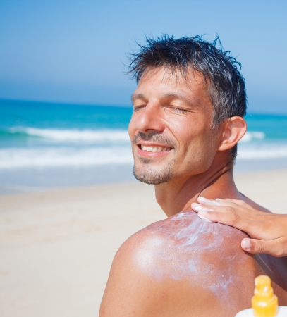 Summer vacation - Happy young man at tropical beach with sunblock cream on the back  photo