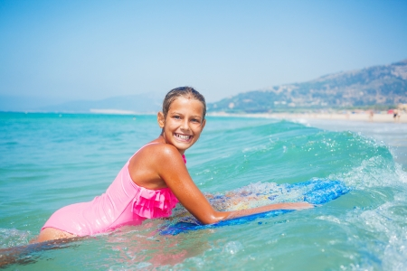Summer vacation - Happy cute girl having fun with surfboard in the ocean photo
