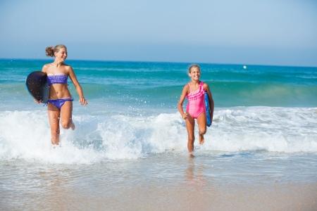 teen girl bikini: Two cute girls in bikini with surfboard running from the ocean