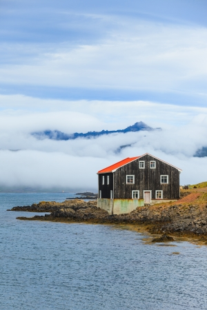 Lonely Black Wooden House at coastline in East Iceland  Vertical view  photo