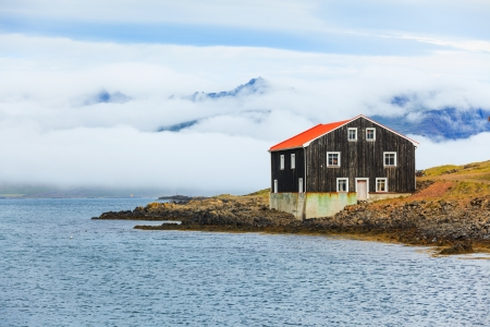 Lonely Black Wooden House at coastline in East Iceland  photo
