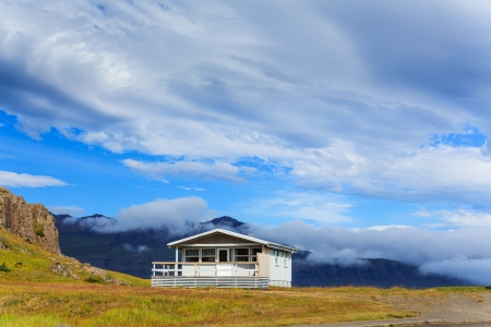 Typical white wooden house against cloudy sky in East Iceland  photo