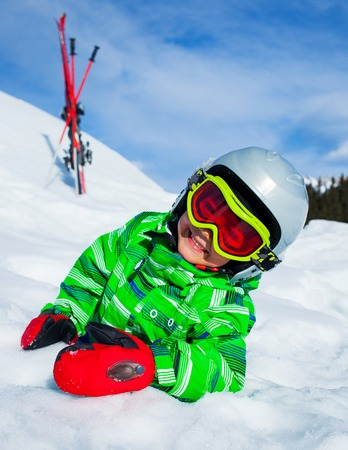 Cute happy skier boy in a winter ski resort  Boy lying in snow  photo
