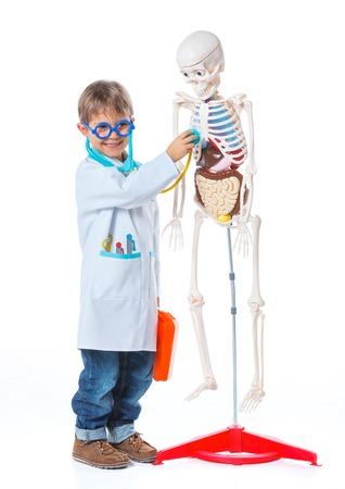 A little smiling doctor with stethoscope and skeleton  Isolated on white background photo