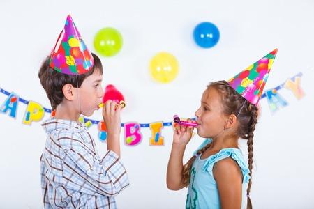 Cute girl and boy having fun at birthday party photo