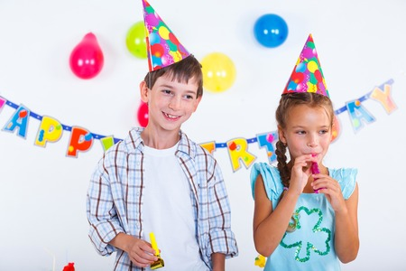 Cute girl and boy having fun at birthday party photo