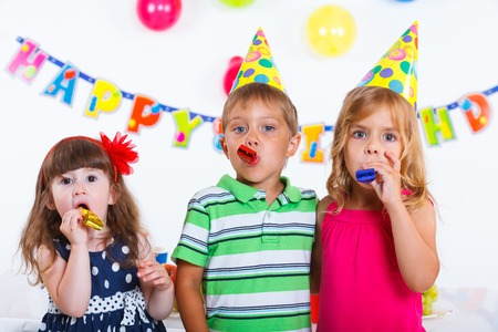kids birthday party: Group of adorable kids having fun at birthday party with birthday cake