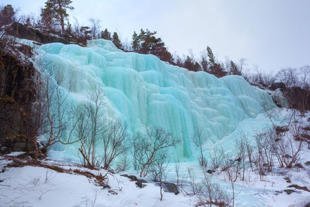 Blue ice and icicles at a frozen waterfall in Norway photo