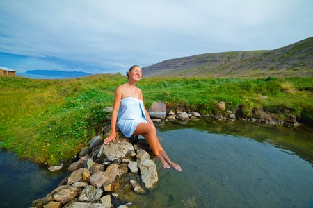 Beautiful young woman in wild geothermal spring, Iceland photo