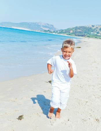 Smiling cute boy runs along the tropical beach  photo