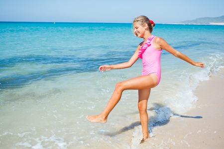 Beautiful happy smiling girl runs along the beach  photo