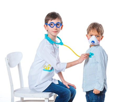 doctor s smock: Portrait of a little smiling doctor with stethoscope and syringe with his patient  Isolated on white background Stock Photo