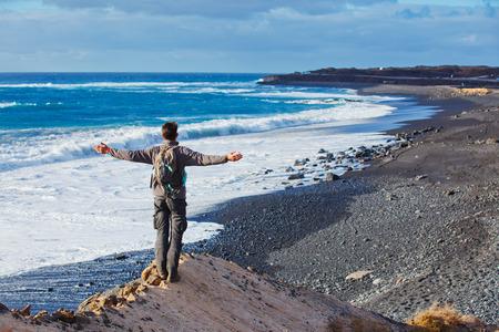 manrique: Tourist man looking to black beach  Lanzarote, Canary Islands, Spain