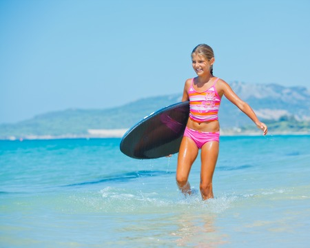Summer vacation - Happy cute girl having fun with surfboard in the ocean