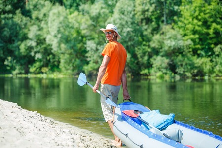 Man paddling a kayak on the river, enjoying a lovely summer day photo