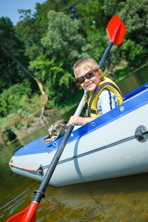 Happy little boy paddling kayak on the river and enjoying a lovely summer day