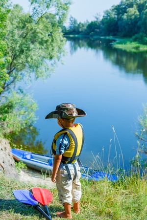 Happy young boy near a kayak on the river, enjoying a lovely summer day photo