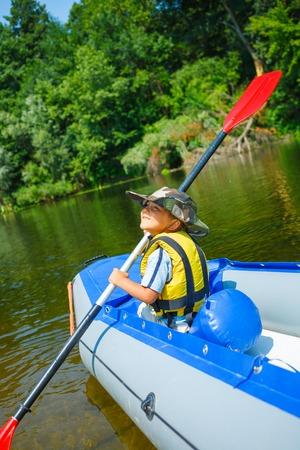 Happy little boy kayaking photo