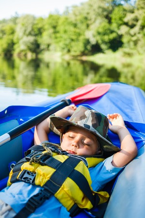 Cute little boy sleeping in kayak on the river at a lovely summer day  photo