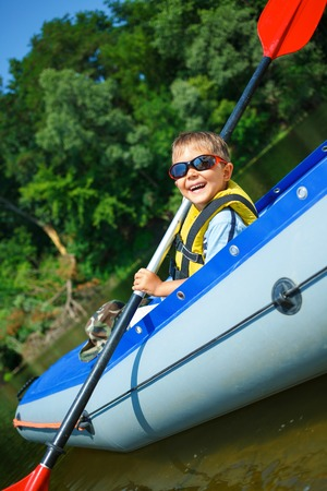 Happy little boy paddling kayak on the river and enjoying a lovely summer day photo