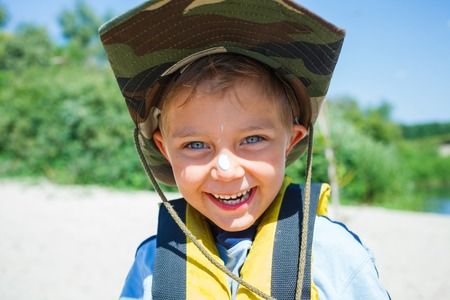 Ready kayaking  Portrait of happy little boy near the river and enjoying a lovely summer day photo