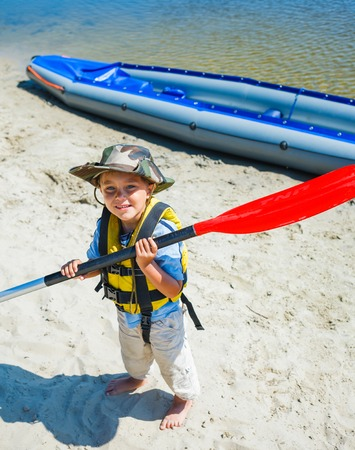 Happy young boy holding paddle near a kayak on the river, enjoying a lovely summer day photo