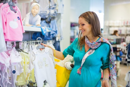 Young pregnant woman choosing newborn clothes at baby shop store Banque d'images