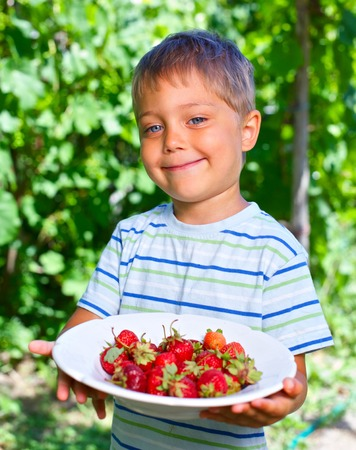 Happy little toddler boy in summer garden with plate of ripe fresh strawberries photo