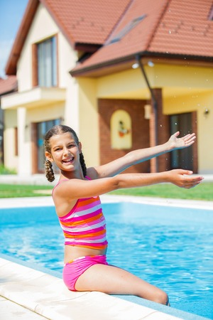 Cute happy girl playing in swimming pool photo