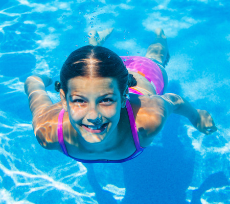 The cute girl swimming underwater and smiling photo