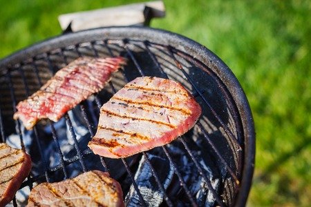 Barbecue on a hot day during the summer vacation on a green grass background  Meat on the grill  photo