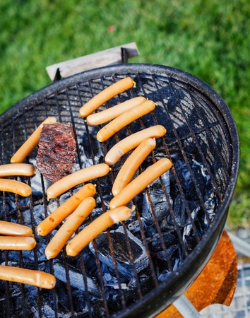 Fresh sausage and hot dogs grilling outdoors on a barbecue grill  photo