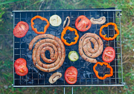 Barbecue on a hot day during the summer vacation on a green grass background. Meat and vegetables on the grill. photo
