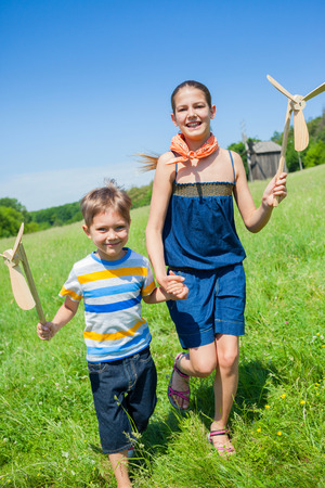 Kids in summer day holds windmill photo