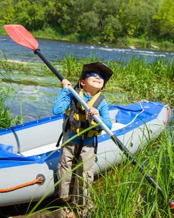 Happy young boy holding paddle near a kayak  photo