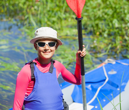 Happy cute girl holding paddle near a kayak  photo