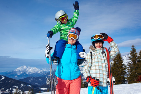 ski goggles: Two kids with mother enjoying winter vacations.