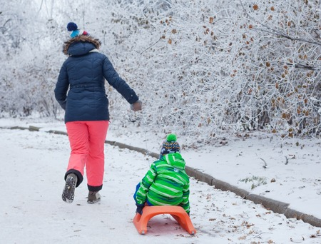 5 6 years: Family having fun with sled in winter park