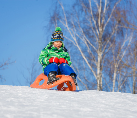 5 6 years: Little boy having fun with sled in winter park