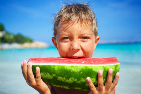 Happy boy on the sea with watermelon Stock Photo