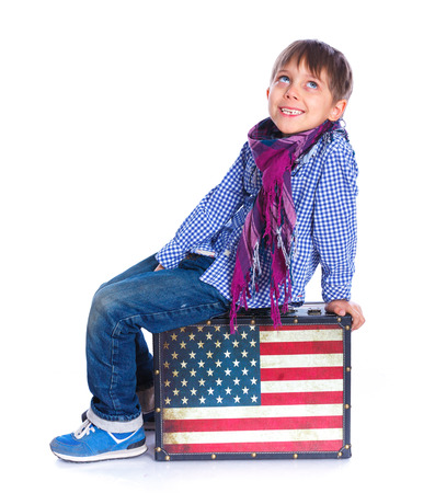 Boy sitting on a case. photo