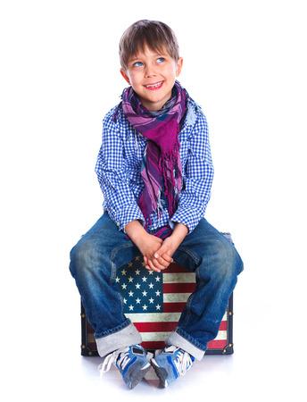 5 6 years: Boy sitting on a case.