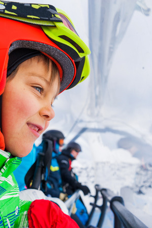 ski run: Ski, skiing - Little skier boy on ski lift Stock Photo