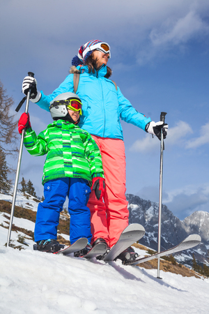 kids at the ski lift: Happy mother with her son on the winter ski vacation.