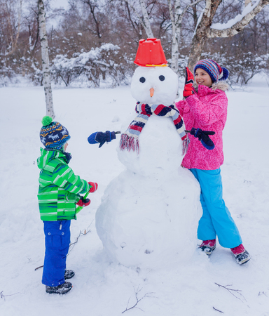ni�os jugando: Happy kids having fun in the snow - making snowman