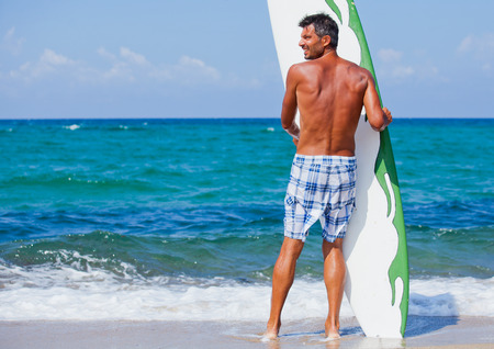 ni�o sin camisa: Man with his surfboard on the beach and looking at the sea