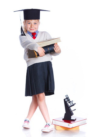 5 year old: Attractive 5 year old girl in  large graduation cap with book and microscope over white background Stock Photo