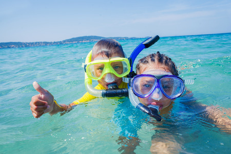 underwater ocean: Joyful sister and brother scuba diving in the clear sea.